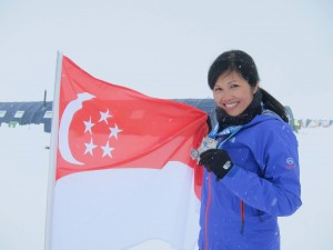 Last leg of an amazing journey completed. Yvonne posing with the Singaporean flag and her Antarctic Ice Marathon medal.