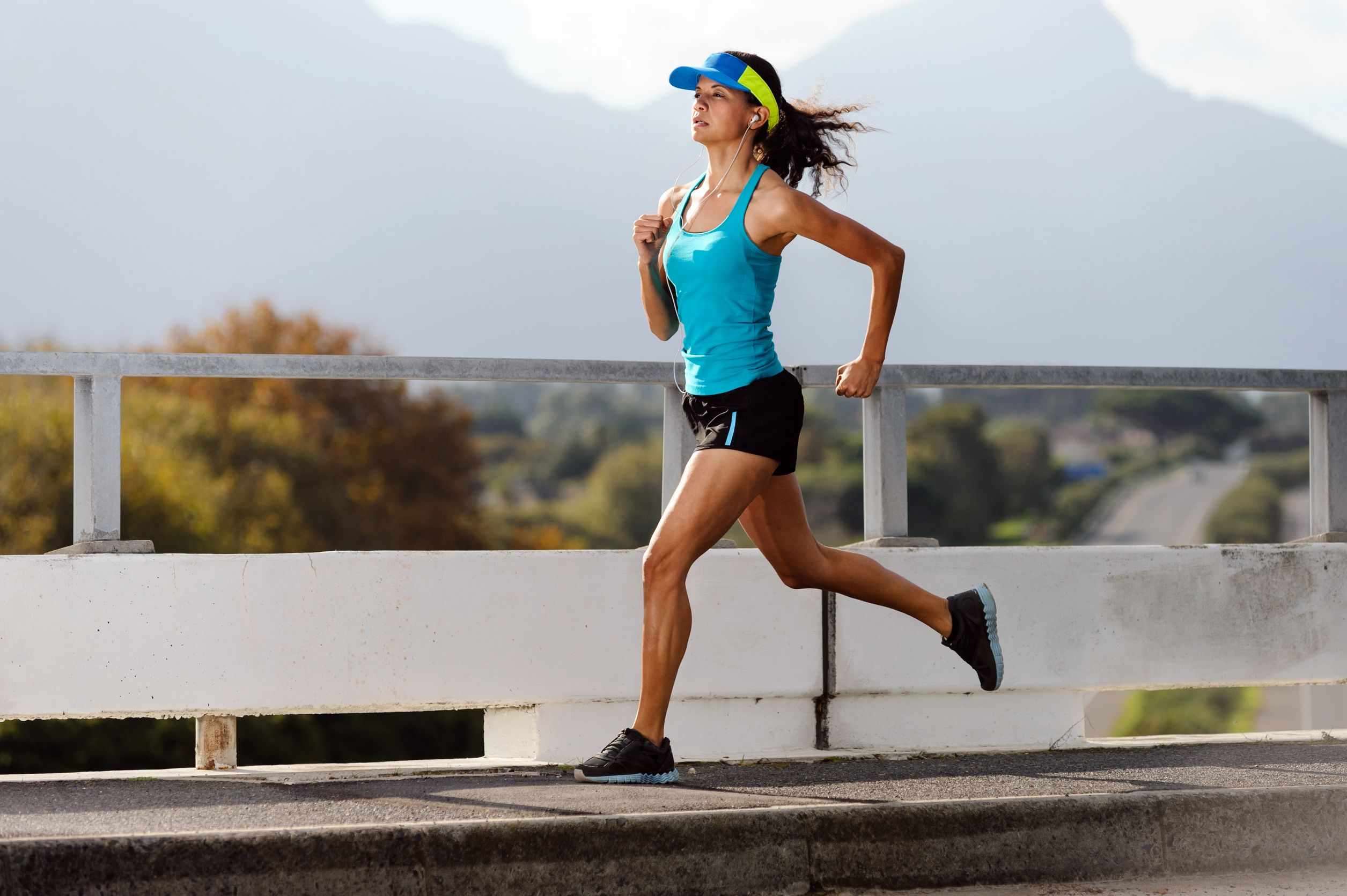 Athlete running on bridge. action shot of runner in mid air. healthy lifestyle fitness woman