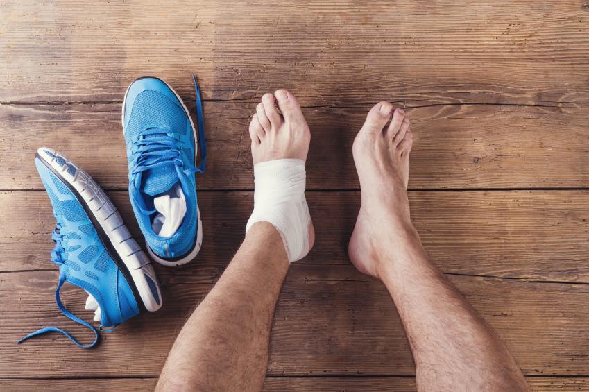 Unrecognizable injured runner sitting on a wooden floor background