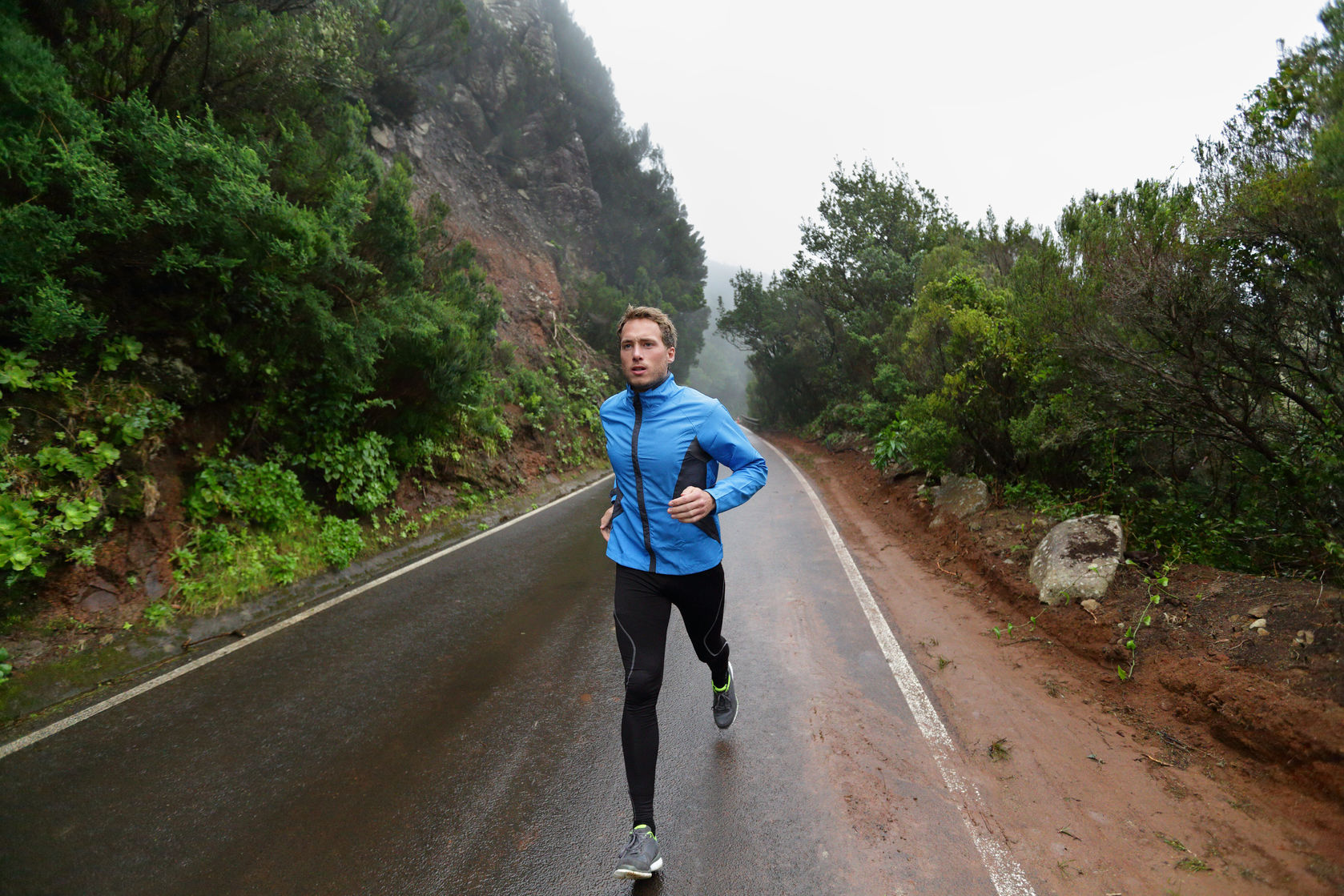Male runner jogging and running on road in rain in jacket and long tights