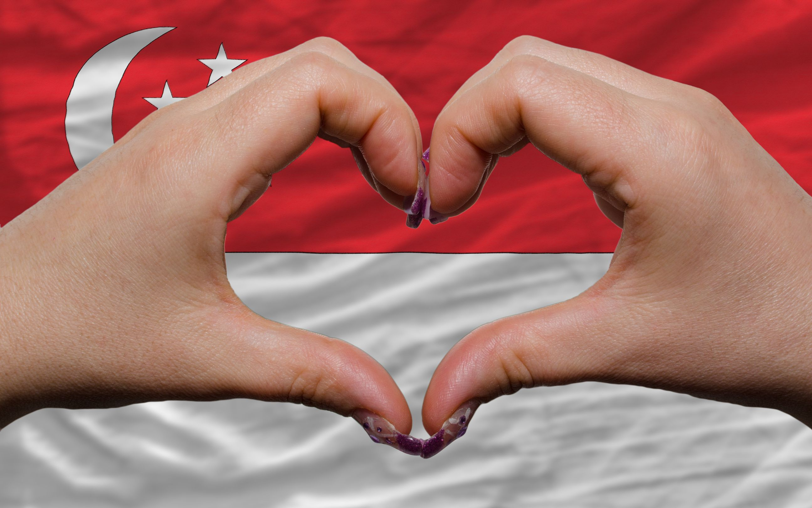 12478749 - gesture made by hands showing symbol of heart and love over national singapore flag