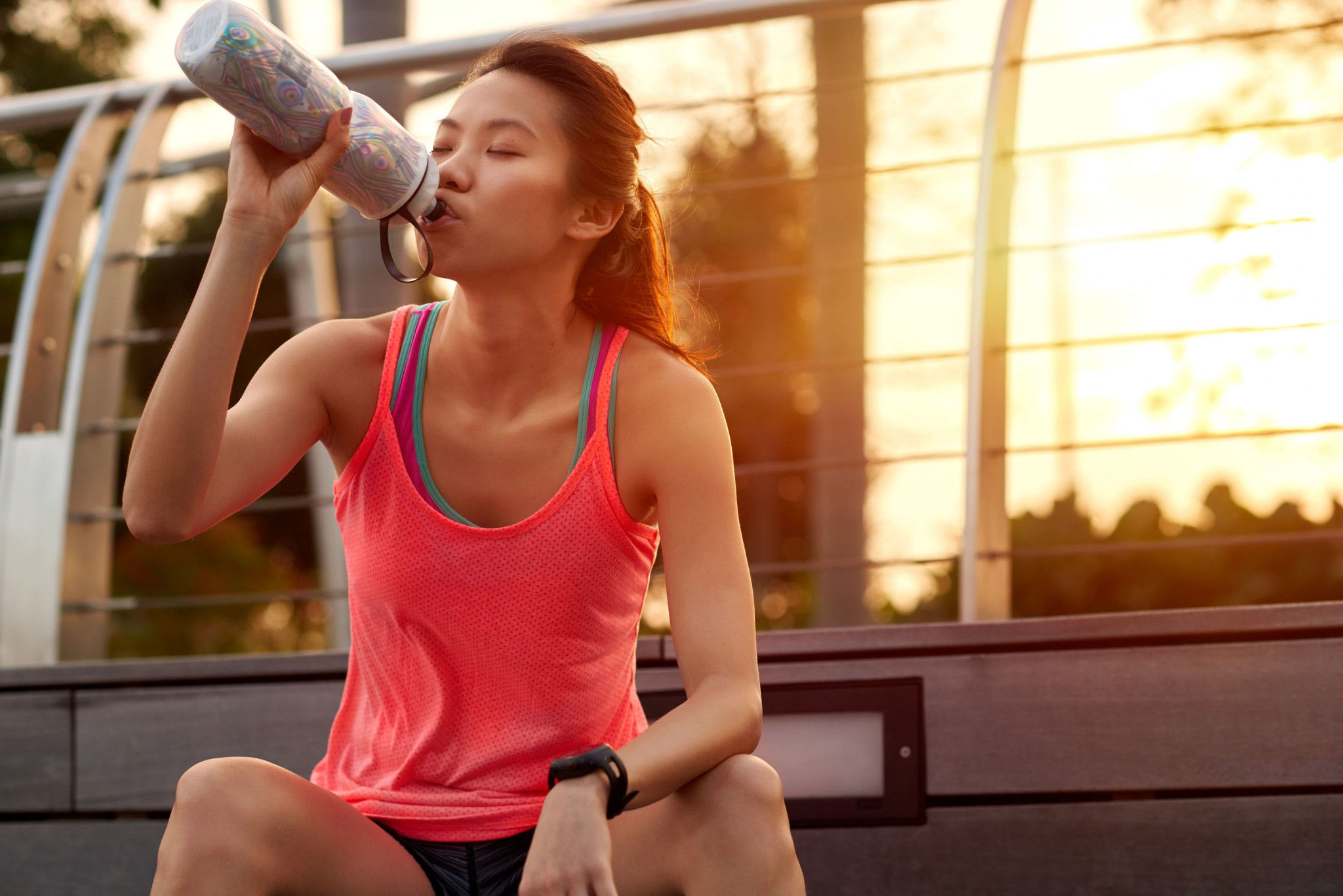 asian-chinese-woman-sitting-outdoors-resting-drinking-water-bottle-after-morning-run