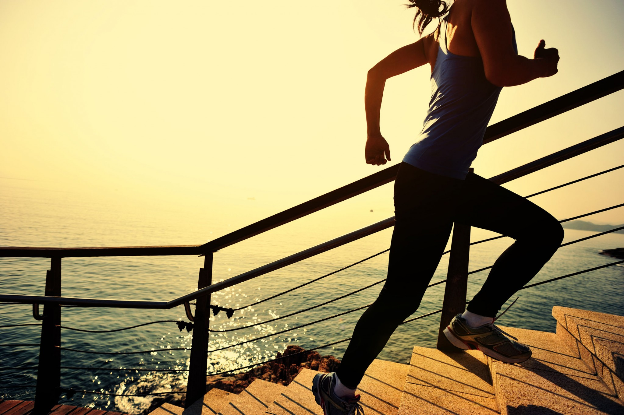 sports-woman-running-up-on-stone-stairs-sunrise