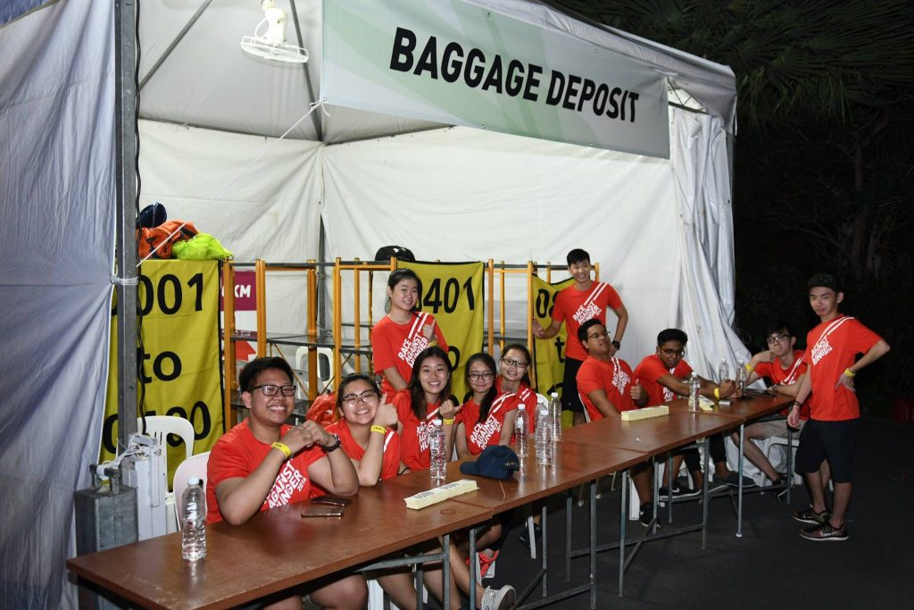 Friendly volunteers at the baggage deposit booth. Credit to Pink Apple Events.