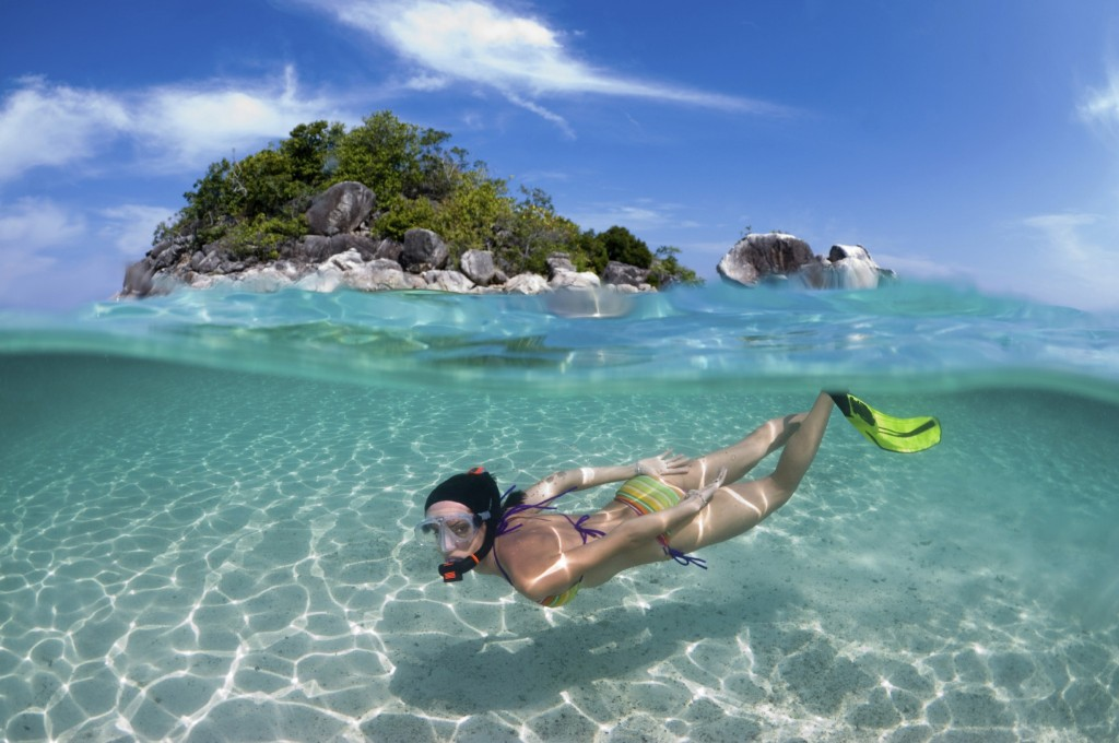 Woman snorkeling in front of small thailand island-iStock_000014822643Large