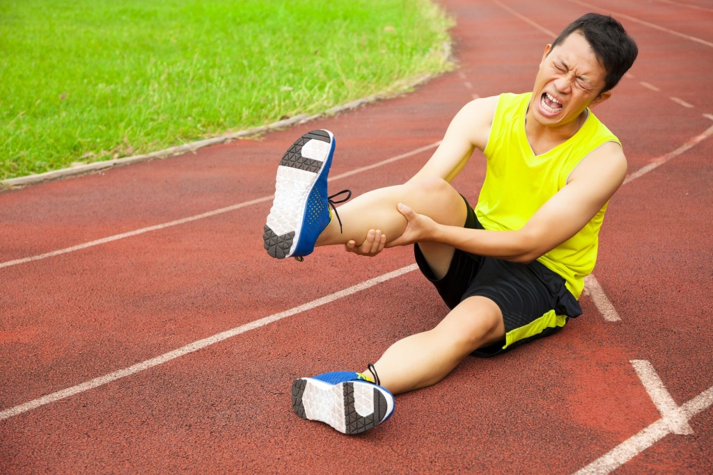 young male runner suffering from leg cramp on the track in the stadium