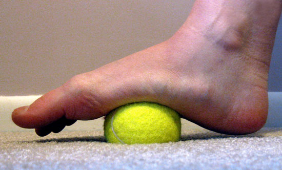 Massaging and stretching foot using a tennis ball, Image credit: Popsugar.com