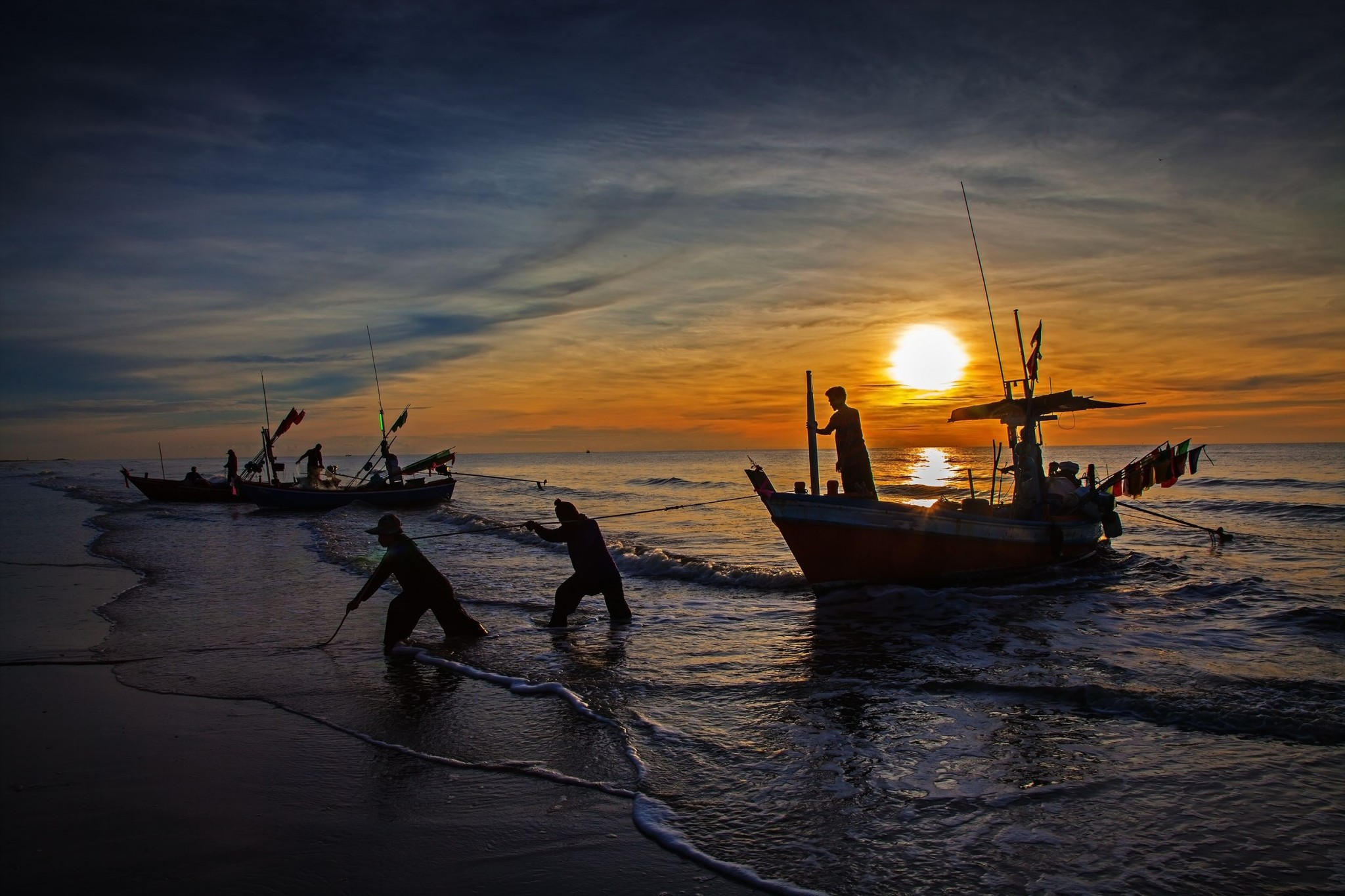 Silhouette of fisherman with sunrise in the background