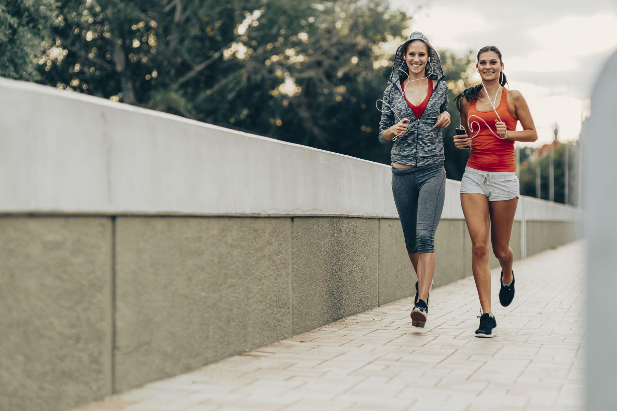 Beautiful women jogging in city while sun is setting down