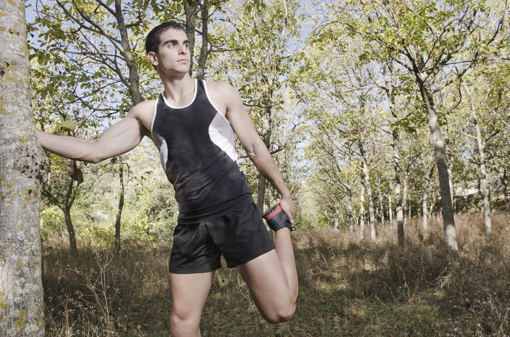 Young runner man warming legs in the forest
